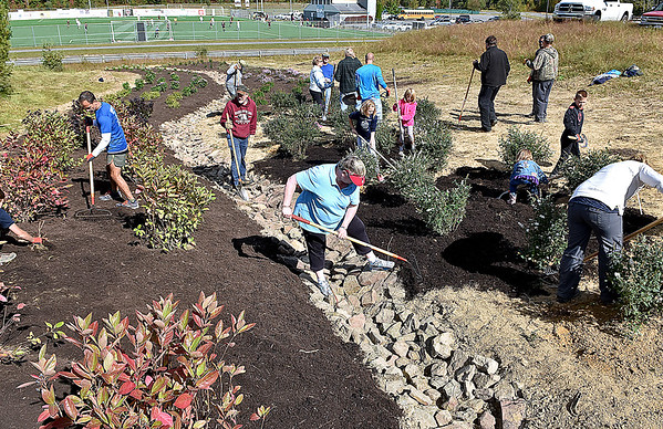 (Brad Davis/The Register-Herald) A small army of Piney Creek Watershed volunteers young and old work to construct a butterfly garden Saturday morning next to the YMCA Paul Cline Memorial Sports Complex.