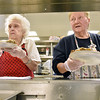 (Brad Davis/The Register-Herald) Volunteers Arvella Phillips, left, and Daisy Shrout work in assembly line fashion as they churn out hot plates of turkey, mashed potatoes, green beans and more to those  who came out for Lewis Christian Community Center's Thanksgiving dinner Thursday afternoon in Oak Hill.