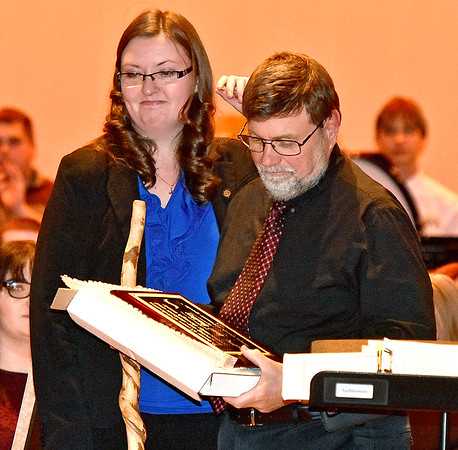 """(Brad Davis/The Register-Herald) Woodrow Wilson band director Bill Bailey looks over a special plaque handed to him by Mary Sue Bailey, band director at Independence Middle School, as he's honored for over 45 years of teaching music during the intermission of Saturday's Southern West Virginia Honor Band performance, where he composed the Gold Band's performance. Bailey, president of the Raleigh County Bandmasters Association, is retiring later this year so Mary Sue Bailey and Liberty High School band director Jeremy Rodriguez presented him with a special plaque with a Hans Christian Andersen quote which reads """"When words fail, music speaks."""""""