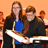 "(Brad Davis/The Register-Herald) Woodrow Wilson band director Bill Bailey looks over a special plaque handed to him by Mary Sue Bailey, band director at Independence Middle School, as he's honored for over 45 years of teaching music during the intermission of Saturday's Southern West Virginia Honor Band performance, where he composed the Gold Band's performance. Bailey, president of the Raleigh County Bandmasters Association, is retiring later this year so Mary Sue Bailey and Liberty High School band director Jeremy Rodriguez presented him with a special plaque with a Hans Christian Andersen quote which reads ""When words fail, music speaks."""