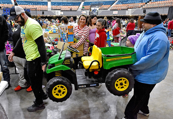 (Brad Davis/The Register-Herald) Volunteer Dave Green, left, helps Glen Morgan resident Eddie Nazario haul out a toy John Deer 4x4 during the annual Mac's Toy Fund event Saturday morning at the Beckley-Raleigh County Convention Center. The gift is destined for his daughters Alana, 6, and Rissa, 5, (not photographed) who won't be suprised as they were on hand to help put it in the car