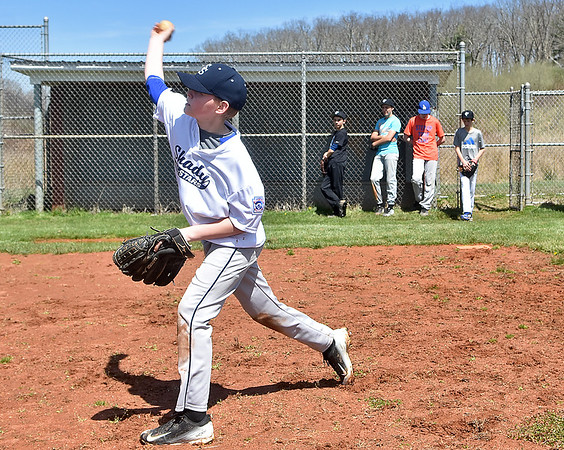 (Brad Davis/The Register-Herald) Baseball player Kasey Estep takes his turn fielding ground balls as his Shady Sharks junior little league teammates (from left in the background) Jacob Showalter, Hayden Johnson, Evan Sinclair and Josh Keiling watch during a practice Sunday afternoon at the Beckley Little League fields.