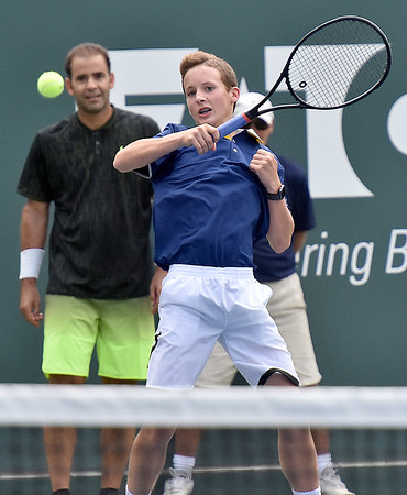 (Brad Davis/The Register-Herald) Ballboy Jaxen Ransom holds his own against James Blake during the Greenbrier Champions Tennis Classic Saturday afternoon in White Sulphur Springs.