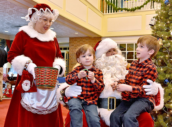 (Brad Davis/The Register-Herald) Mrs. Claus reacts and Santa pays close attention as seven-year-old Andrew Blake, right, recites item after item - including a jack hammer - on his long wish list while little brother Brandt, 4, is already enjoying a candycane after conveying his more simplified requests during the Lewisburg Holiday Festival Saturday afternoon. City National Bank hosted Santa and Mrs. Claus.