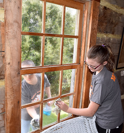 (Brad Davis/The Register-Herald) Karhlyle Hopkins takes to outside while Rachael Wriston gets the inside of a window as the two Bradley Elementary 5th graders clean in the post office in the back yard of Wildwood House during a Spring cleanup Saturday afternoon.