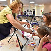 (Brad Davis/The Register-Herald) Volunteer painting teacher Debbie Lester shows a few color mixing tricks to young artists Kaylee (near), 10, and Taylor Wills, 17, during the Beckley Art Center's Family Art Festival Saturday afternoon.