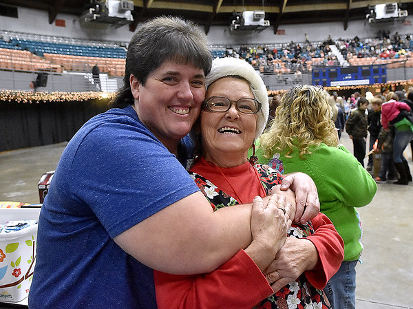 (Brad Davis/The Register-Herald) Volunteers Chris Gill, left, and Reba Crawford share a hug and a quick photo pose during the annual Mac's Toy Fund event Saturday morning at the Beckley-Raleigh County Convention Center.