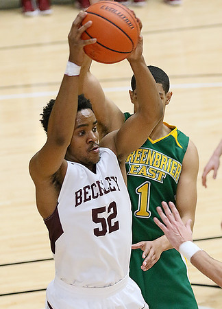 (Brad Davis/The Register-Herald) Woodrow Wilson's Breland Walton pulls down an offensive rebound as Greenbrier East's Jasiah Rawls defends during the Flying Eagles' Sectional Championship victory over the Spartans Friday night at the Beckley-Raleigh County Convention Center.
