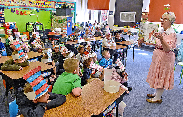 (Brad Davis/The Register-Herald) Valerie Hartling (right), a volunteer with Read Aloud West Virginia, reads a Dr. Suess tale to Stephanie Rubin's 1st grade class at Crescent Elementary School Thursday afternoon. Yesterday was national Dr. Suess Day, which celebrates the life and work of the late Theodor Suess Geisel (1904-1991) with classroom readings and Cat-in-the-Hat related activities in schools everywhere.