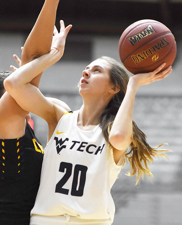WVU Tech's (20) goes up for a shot over a Carlow player during the third quarter of their basketball game in Beckley Tuesday. (Chris Jackson/The Register-Herald)