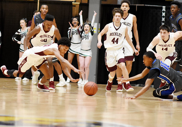 Woodrow Wilson's Mikey Penn (20) and Capital's (10) dive for a loose ball that Woodrow recovered for a fast break during the second quarter of their sectional championship basketball game Tuesday in Beckley. (Chris Jackson/The Register-Herald)