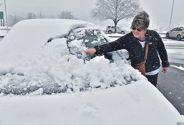 (Brad Davis/The Register-Herald) Mount Vernon, Kentucky resident Melinda Gilliam brushes wet, heavy snow from her car as she deliberates on whether or not to brave the highway back home or stay in Beckley after attending a beekeeping event at Tamarack Saturday afternoon as the latest snowstorm hit.