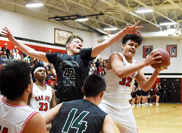 Oak Hill's (32) grabs an offensive rebound over Wyoming East's Anthony Martin (42) during the second quarter of their basketball game Tuesday in Oak Hill. (Chris Jackson/The Register-Herald)