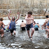 People run out and in of the icy New River with temperatures in the low teens during the annual New Year's Day Polar Plunge at Fayette Station in Fayetteville on Monday. Participants had to work to break ice in order to run into the river. (Chris Jackson/The Register-Herald)