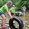 (Brad Davis/The Register-Herald) 10-year-old Annabell Lemon rolls a tire up the bank as fellow volunteers Lisa Snodgrass, middle, and Amanda Lemon work to clean up a section of the Peach Tree Creek and falls area during a cleanup project Saturday afternoon near Naoma.