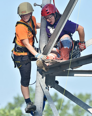 (Brad Davis/The Register-Herald) Volunteer Alexis Franklin, right, screams wildly as she plays the role of a badly injured worker high atop a cell phone tower as trainees from Team WV Wild Med are tasked with reaching, treating and rescuing her during a high intensity, scenario-based simulation that was part of the annual Battle in the Gorge E.M.S. and Fire Competition Sunday morning on the grounds of Fayette County 911. Participating teams compete and train in scenarios that test both individual and combined rescue disciplines such as vertical rescue, paramedic, basic EMT and vehicle extrication. Teams don't know what scenario they will be thrown into until they arrive on the scene.