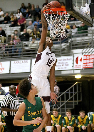 (Brad Davis/The Register-Herald) Woodrow Wilson's Ty Walton dunks the ball as Greenbrier East's Steven Winnings can only watch Saturday night at the Beckley-Raleigh County Convention Center.