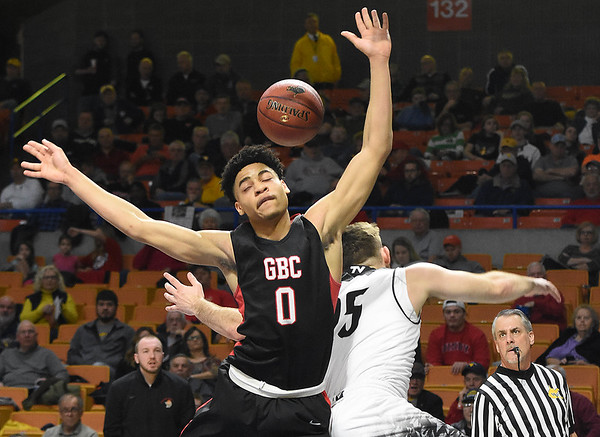 Jat Moore, left, of Greater Beckley Christian, left, fights for a rebound against, Levi Davis, of Tug Valley  during the quarter-final game of the Class A Boys State Basketball Tournament held at the Charleston Civic Center. Tug Valley won 83-52<br /> (Rick Barbero/The Register-Herald)