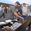 (Brad Davis/The Register-Herald) Indy's designated grill master Jamie Bolen cooks up burgers Friday night in Coal City.