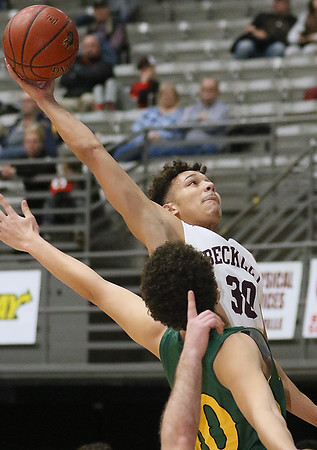 (Brad Davis/The Register-Herald) Woodrow Wilson's Eddie Christian reaches to get ahold of a high inbound pass from Ty Walton that would fall for two points as Greenbrier East's Justin Davis defends Wednesday night at the Beckley-Raleigh County Convention Center.