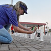 (Brad Davis/The Register-Herald) Six-year cancer survivor and one of the event organizers Sandra McBride-Compton snaps photos of all the different luminaries on display prior to lighting them during the Relay For Life Friday night atop Beckley's Intermodal Gateway. Both of her parents were lost to the terrible disease.