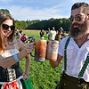 (Brad Davis/The Register-Herald) Sporting proper German attire, beer lovers Derrick O'Neal and Rachel Simms cheers one another as they enjoy the festivities during Weathered Ground Brewery's 2nd Annual Oktoberfest Saturday afternoon in Cool Ridge.