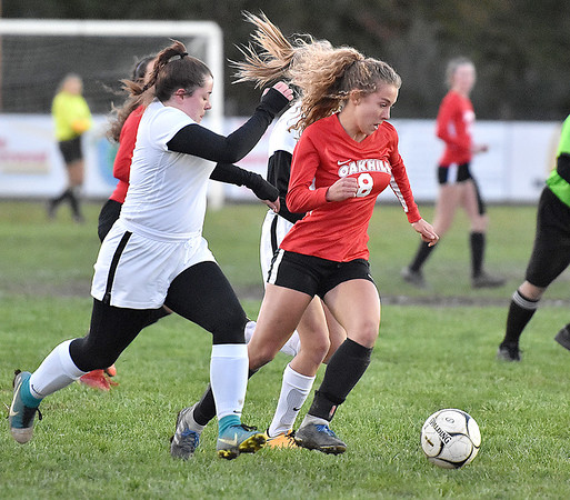 (Brad Davis/The Register-Herald) Oak Hill's Kiya Babkirk cuts between Oak Hill defenders Sarah Stamper, left, and Erin O'Sullivan Wednesday night in Oak Hill.