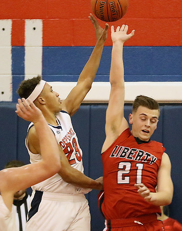 (Brad Davis/The Register-Herald) Independence's Niko Burgess drives and scores as Liberty's Ethan Hill defends Friday night in Coal City.