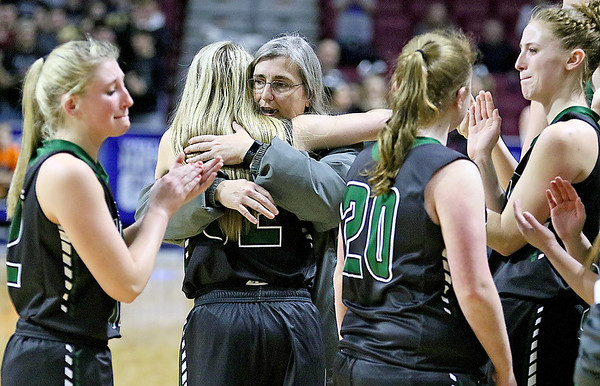 (Brad Davis/The Register-Herald) Wyoming East coach Angie Boninsegna consoles senior Gabby Lupardus and the rest of her team during the closing moments of the Lady Warriors Class AA State Championship game loss to North Marion Saturday afternoon at the Charleston Civic Center.