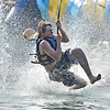 (Brad Davis/The Register-Herald) Shady Spring resident Tristen Tate sends water flying as he splashes down at the end of a zipline run at Ace Adventure Resort Sunday afternoon.