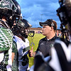 (Brad Davis/The Register-Herald) Wyoming East players and coaches strategize prior to the kickoff Friday night in Lindside.