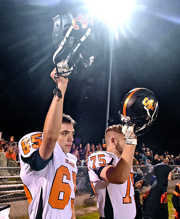 (Brad Davis/The Register-Herald) Summers County players Nicholas Willey, left, and Dustin Stephens hold up their helmets as the their game at Meadow Bridge kicks off Friday night in Meadow Bridge.