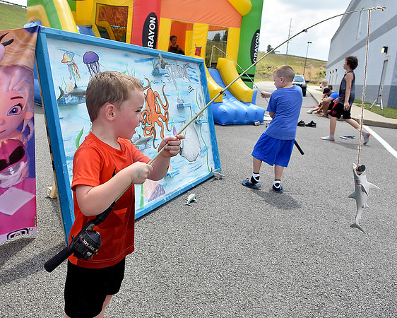 (Brad Davis/The Register-Herald) Four-year-old Mason Russell catches a shark, one of several on the day, as he plays a fishing game during the Kid's Quest Carnival Saturday morning at Marquee Cinemas