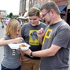 (Brad Davis/The Register-Herald) 10-year-old Mallory Toney gets a forkfull of what dad Shawn is having as 13-year-old brother Luke looks on as the Beckley residents eat while they walk along Neville Street during Taste of Beckley Saturday evening.