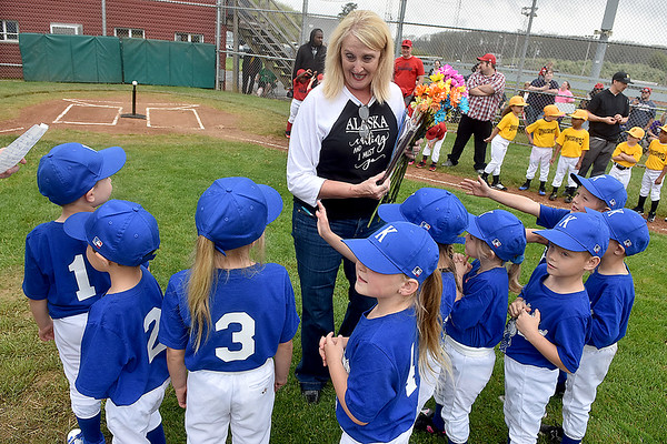 (Brad Davis/The Register-Herald) 30-plus-year Beckley Little League volunteer Lee Ann Myles, middle, is suprised with flowers and a special plaque by players and coaches from the Knights during team introductions, part of Beckley Little League's Tee Ball Opening Day ceremonies Saturday afternoon.