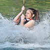 (Brad Davis/The Register-Herald) Fairmont resident Ariel Stern sends water flying as she splashes down at the end of a zipline run at Ace Adventure Resort Sunday afternoon.