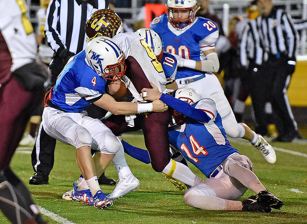 (Brad Davis/The Register-Herald) Sherman ball carrier J.T. Hensley is gang tackled my Midland Trail defenders (from left) Nathan Hanshew, Morgan Ferris and Trevor Maichle Friday night in Fairlea.