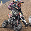 (Brad Davis/The Register-Herald) Daniels resident Connor Morehead (#24), 13, cuts around an opponent as he competes in a pit bike division race during the weekend's Tristate MX dirt bike racing event Saturday night at the Beckley-Raleigh County Convention Center.