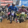 (Brad Davis/The Register-Herald) A pack of racers on pit bikes ranging in age from 13 to 30 skip over a section of the course at top speed during the weekend's Tristate MX dirt bike racing event Saturday night at the Beckley-Raleigh County Convention Center.
