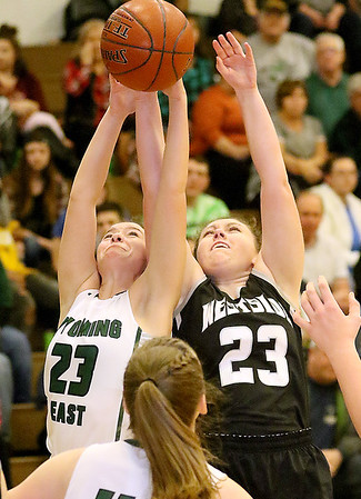 (Brad Davis/The Register-Herald) Wyoming East's Kaytlin Daniels and Westside's Allison Cassell leap to grab a rebound Thursday night in New Richmond.
