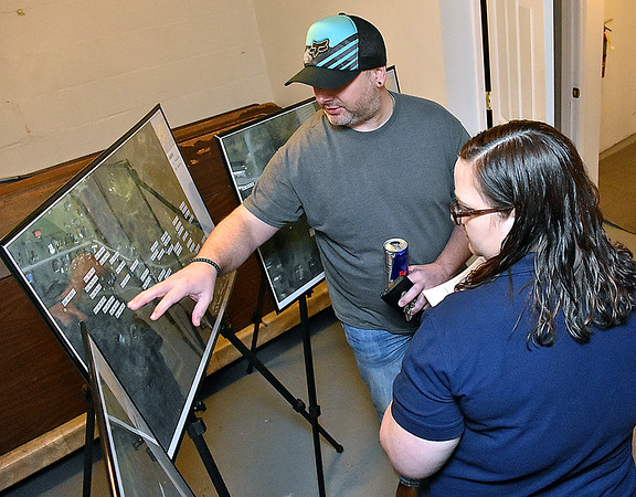 (Brad Davis/The Register-Herald) Minden resident Michael Scarbro talks with EPA On-Scene Coordinator Melissa Linden as the two look over aerial maps detailing some of the soil sampling work done so far in investigating the presence of PCB's in the town during the second day of public meetings Saturday morning at New Beginning Apostolic Church.