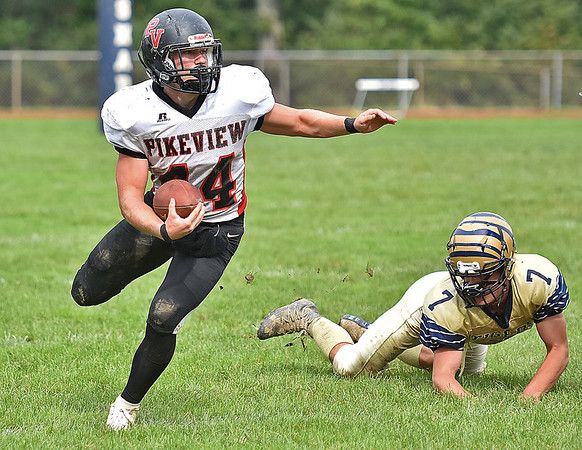 (Brad Davis/The Register-Herald) PikeView's Evan Rose turns upfield after shaking a tackle from Shady Spring defender Daylon Toms in the backfield Saturday afternoon in Shady Spring.