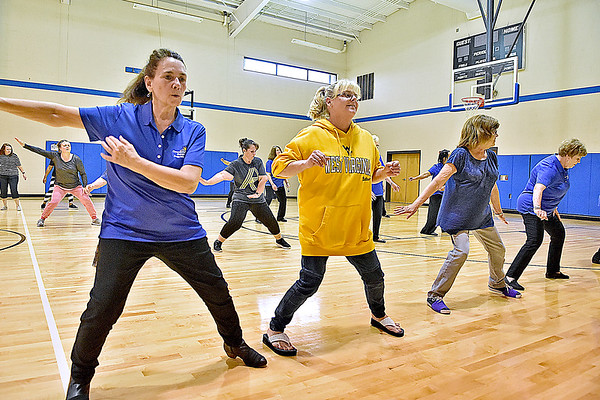 (Brad Davis/The Register-Herald) Raleigh County Commission on Aging employee Linda Scott, left, takes part with fellow employees and participants in a moderately paced line dance session as they workout during a free community fitness and wellness event aimed towards older adults Saturday morning at Memorial Baptist Church.