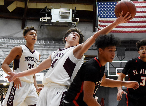 Woodrow Wilson's Danny Bickey (44) grabs a offensive rebound over St. Albans Reggie Jackson (4) during the first quarter of their basketball game Monday in Beckley. (Chris Jackson/The Register-Herald)