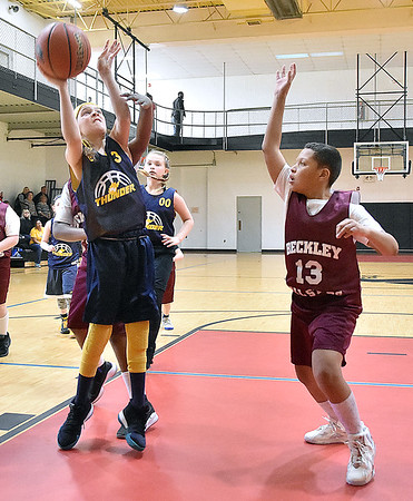 (Brad Davis/The Register-Herald) WV Thunder's (Huntington) Addison Godbey drives to the basket as Beckley White's Nisaiah Pryor defends during a fourth grade Biddy Buddy Tournament game Friday afternoon at the YMCA of Southern West Virginia. WV Thunder won the game by a wide margin.