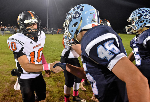 (Brad Davis/The Register-Herald) Meadow Bridge's Caleb Richmond, right, reaches out to shake hands with visiting Summers County player Timmy Persiani as the two teams meet at midfield for the coin toss prior to the start of their game Friday night in Meadow Bridge.