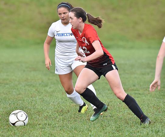 (Brad Davis/The Register-Herald) Oak Hill's Courtney Smith speeds up the field as Princeton's Haley Mathena pursues Thursday evening in Oak Hill.
