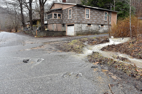 (Brad Davis/The Register-Herald) Runoff from Saturday's rain continues spilling out of ditches and into roadways along a section of Coal City Road near Rhodell Sunday afternoon.