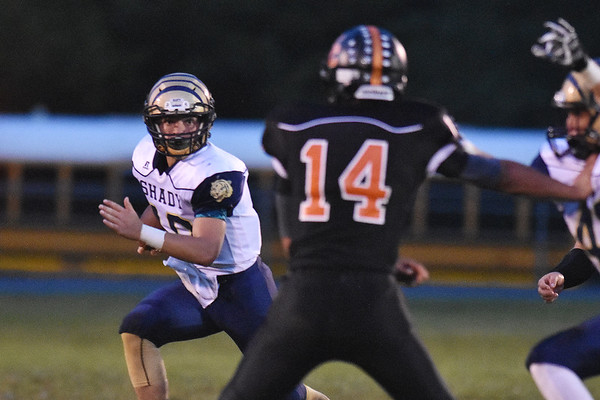 Shady Spring quarterback Drew Clark (10) looks to get past Summers County's Christian Pack (14) during their high school football game Friday in Hinton. (Chris Jackson/The Register-Herald)
