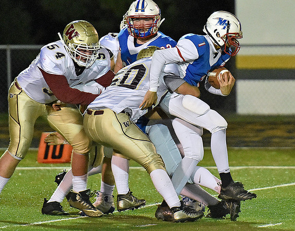 (Brad Davis/The Register-Herald) Midland Trail quarterback Christopher Vines is wrapped up by Williamstown defender Ryan Brown Friday night in Fairlea.